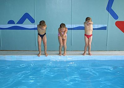 Three Kids Standing On Edge Of Pool